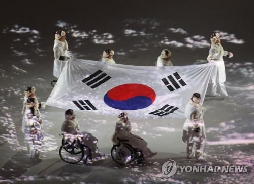 دخول المنتخب الأولمبي الجنوبي إلى الملعب الأولبي يحملون العلم كوريا الجنوبية