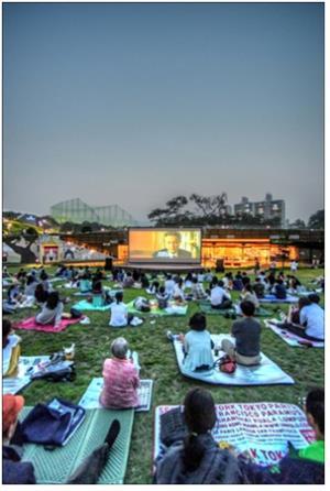 도심 속 푸른 잔디 위에서 영화 피크닉 즐겨요