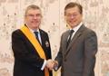 الرئيس مون يصافح رئيس اللجنة الأولمبية الدولية