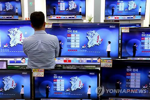 资料图片:4日,首尔一位市民在一家商场观看三家主流电视台公布的地方选举出口民调结果。(韩联社)