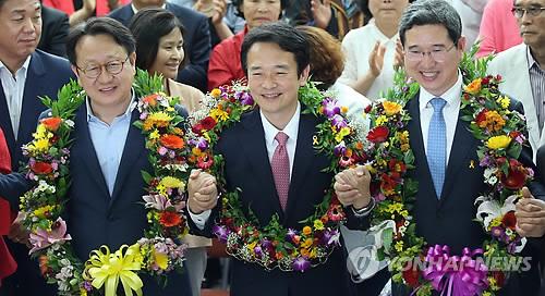 新世界党候选人南景弼(中)当选京畿道知事。图为南景弼5日上午在位于京畿道水原市的选举办公室与同仁们合影庆祝。(韩联社)