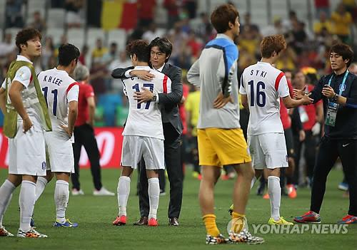 韩国国家男子足球队主教练洪明甫在比赛结束后拥抱并安慰队员。(韩联社)