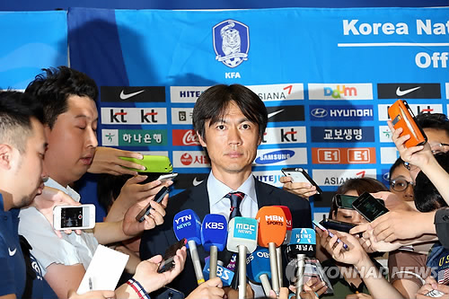 30日凌晨,韩国队主教练洪明甫在仁川机场接受媒体采访。(韩联社)