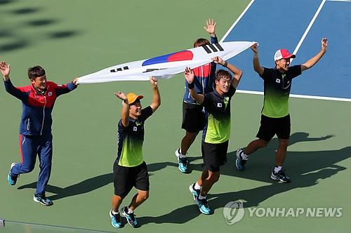 资料图片:韩国队在仁川亚运软式网球男团赛中摘金后共庆获胜。(韩联社)