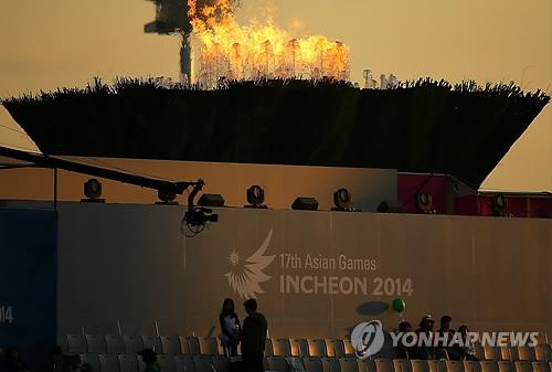 资料图片:夕阳下的仁川亚运圣火即将熄灭(韩联社)