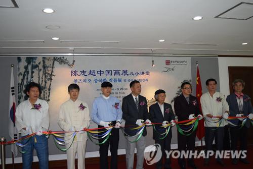19日,在首尔中国文化中心,贵宾为陈志超中国画展剪裁。(韩联社)