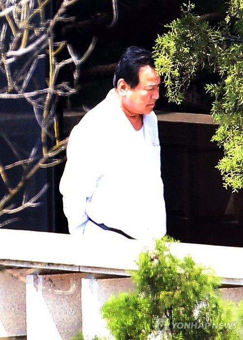 Prime Minister Lee Wan-koo is pictured walking on the terrace of his residence in central Seoul on April 21, 2015, as reporters wait outside of it to see whether he will come out of it. (Yonhap)