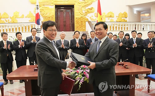 South Korean Trade, Industry and Energy Minister Yoon Sang-jik (L) and his Vietnamese counterpart, Vu Huy Hoang, shake hands after signing a bilateral free trade agreement in Hanoi on May 5, 2015. The two countries seek to implement the deal by the year`s end. (Yonhap) (END)