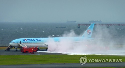 Firefighters put out a fire on a Korean Air plane on the runway of Haneda Airport in Tokyo on May 27, 2016, in this photo released by Kyodo News. The left wing of the plane bound for Seoul caught fire before takeoff, but all 319 passengers and crew were safely evacuated, according to the Japanese news agency. (Yonhap)