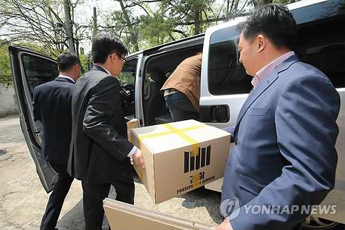 Les officiels du Parquet montent sur une voiture après avoir perquisitionné la résidence de Yoo Byung-eun