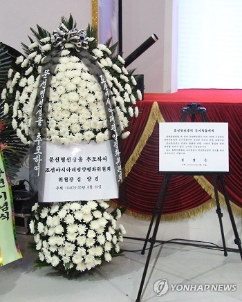 La couronne de fleurs (à gauche) envoyée par le secrétaire du Parti du travail du Nord, Kim Yang-gon, et le message envoyé par le dirigeant nord-coréen Kim Jong-un à l'occasion du troisième anniversaire de la mort du fondateur de l'Eglise de l'unification, Moon Sun-myung.