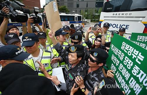 日本大使館に抗議書簡を伝達しようとして警察に制止される団体会員ら=22日、ソウル(聯合ニュース)