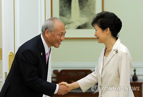 舛添知事と握手する朴大統領(右)=25日、ソウル(聯合ニュース)