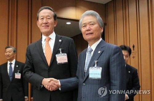 握手を交わす許会長(左)と榊原会長=(聯合ニュース)