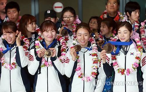 Los atletas surcoreanos posan con medallas de chocolate en el Aeropuerto Internacional de Incheon.
