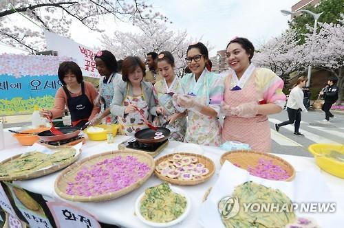 4月5日,在位于韩国釜山的新罗大学,外国留学生制作樱花煎饼。(韩联社)