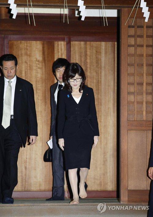 12月29日,日本防卫大臣稻田朋美(中)参拜靖国神社。(韩联社/法新社)