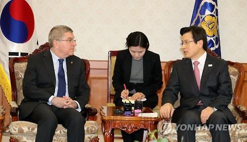 3月14日,在首尔,代行总统职权的韩国总理黄教安(左)会见国际奥委会主席托马斯・巴赫。(韩联社)