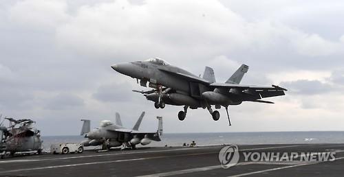 """3月14日,F/A-18战斗机在""""卡尔・文森""""号核动力航母上降落。(韩联社)"""