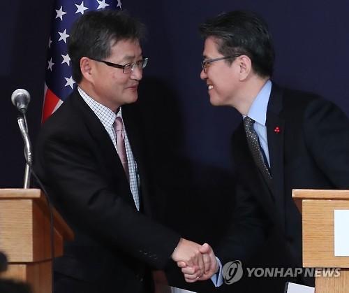 资料图片:2016年12月13日,在首尔小公洞乐天酒店,金烘均(右)和约瑟夫・尹在朝核问题六方会谈韩美日团长共同会见记者后握手致意。(韩联社)