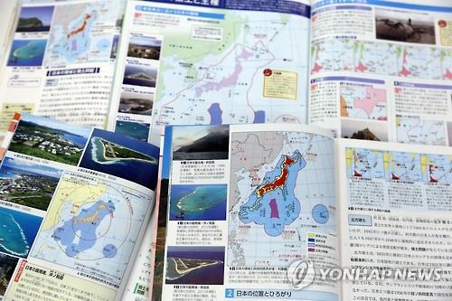 """资料图片:图为去年日方审定通过的教科书。书中写道""""竹岛是日本固有领土,但非法占岛的韩国声称拥有其主权。""""(竹岛是日本对独岛的称呼)。(韩联社)"""
