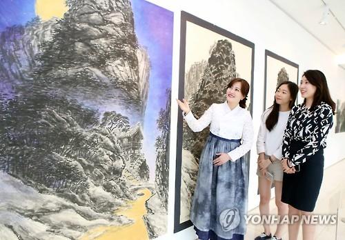 资料图片:柳在春(左一)在画展上向访客介绍作品。(韩联社)