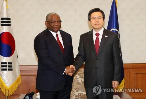 4月18日,在韩国中央政府首尔办公楼,代总统黄教安(右)与到访的安哥拉外长希科蒂握手合影。(韩联社)