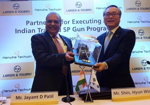 4月21日,在新德里,韩华Techwin代表理事申铉宇(右)与印度拉森特博洛公司(L&T)副总经理Jayant D Patil签署K-9自行火炮出口合同后手举K-9自行火炮模型合影留念。(韩联社)
