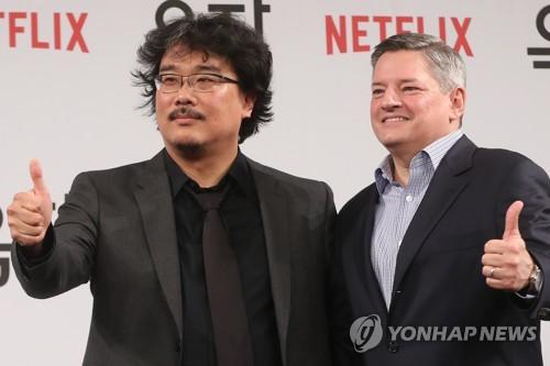 5月15日,韩国导演奉俊昊(左)和Netflix首席内容官泰德・萨兰多斯在《玉子》记者会上摆姿势供媒体拍照。(韩联社)