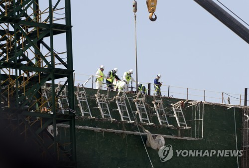 """资料图片:""""世越""""号现场处理本部工作人员在船体右舷进行失踪者遗体搜寻工作。(韩联社)"""
