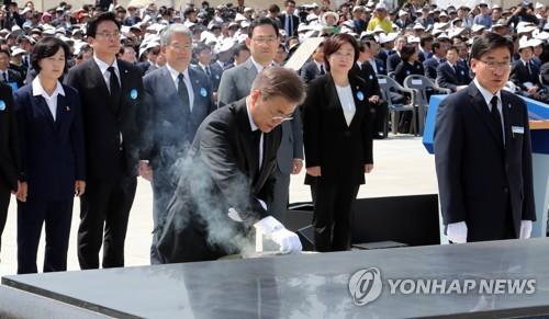 5月18日上午,在光州5・18墓地,文在寅出席5・18民主化运动37周年纪念仪式时焚香悼念。(韩联社)