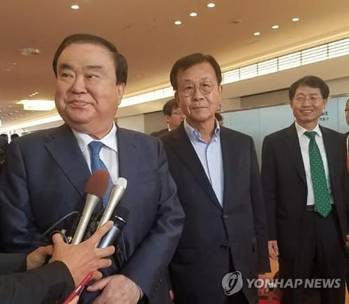 5月17日,在东京羽田机场,韩国总统特使文喜相(左)抵达日本。(韩联社)