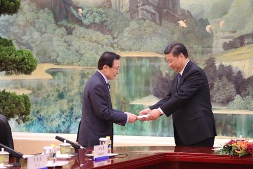 5月19日上午,在人民大会堂,中国国家主席习近平(右)接过韩国总统特使李海瓒捎来的总统亲笔信。(韩联社)