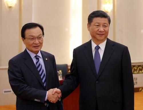 5月19日,在北京人民大会堂,韩国总统特使、前国务总理李海瓒(左)同中国国家主席习近平握手合影。(韩联社)