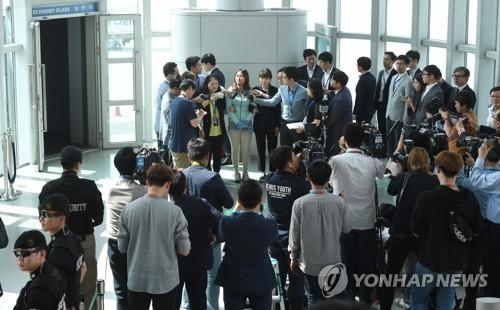 5月31日下午,在仁川机场,崔顺实的女儿郑某戴着手铐答记者问。(韩联社)