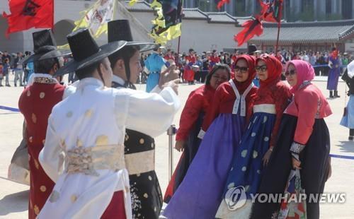 资料图片:穆斯林游客在韩国旅游景点拍照留念。(韩联社)