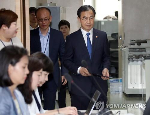 7月17日上午,在首尔市的中央政府办公楼,韩国统一部长官赵明均(系蓝色领带)进入记者会会场。(韩联社)