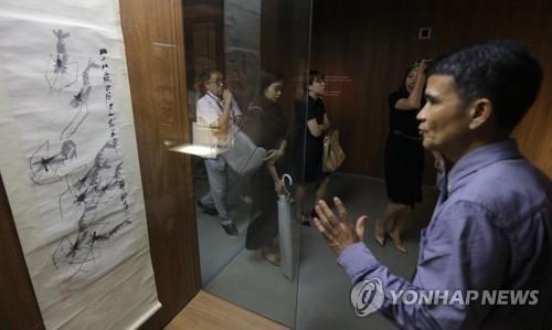 7月31日,齐白石艺术作品展在艺术殿堂开幕,中国湖南省博物馆书画业务主管刘刚(右)正在讲解齐白石的作品。(韩联社)