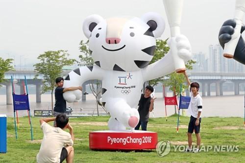 资料图片:市民与平昌冬奥会的吉祥物Soohorang雕像合影留念。(韩联社)