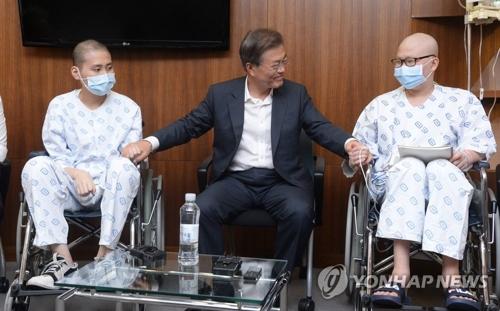 8月9日,文在寅(左二)访问位于首尔瑞草区的首尔圣母医院,并与病人亲切交谈。(韩联社)