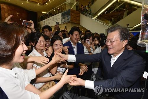 资料图片:韩国总统文在寅(右)与民众握手致意。(韩联社)