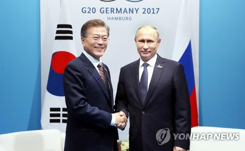 资料图片:当地时间7月7日,在德国汉堡,韩国总统文在寅(左)和俄罗斯总统普京在首脑会谈前亲切握手。(韩联社)