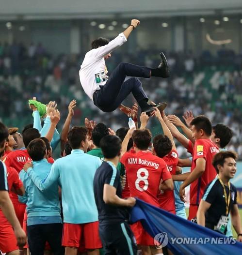 当时时间9月5日晚,在塔什干本尤德科体育场,韩国客场挑战乌兹别克斯坦队,并以0比0战平,最终晋级世界杯。图为队员们将主帅申台龙高高抛起以示庆祝。(韩联社)