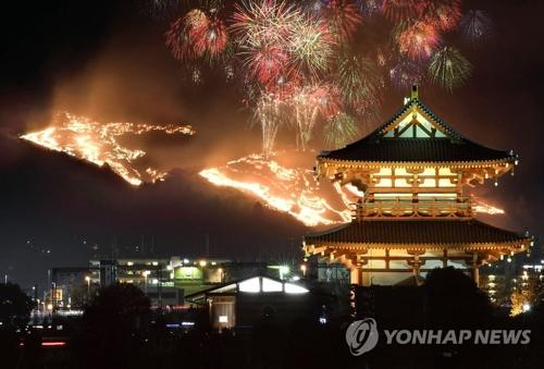 """2017年1月28日,在日本千年古都奈良,烧山节""""若草山烧山""""隆重举行。图右侧为平城宫迹朱雀门。"""
