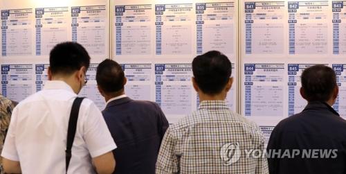 资料图片:求职者在查看招聘公告。(韩联社)