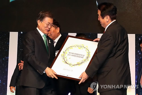 9月27日,在首尔蚕室乐天酒店,韩国总统文在寅(左)出席第11届世界韩人日纪念活动暨2017世界韩人会长大会开幕式,从世界韩人会会长处接到和平桂冠相框。(韩联社)