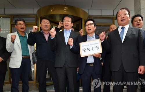 10月12日上午,在首尔市的中央政府办公楼,申汉龙(前排右一)等园区企业家前来申请访问朝鲜。(韩联社)