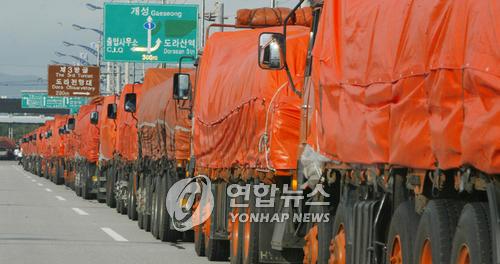 资料图片:满载援朝物资的韩国卡车排队等待出境。(韩联社)