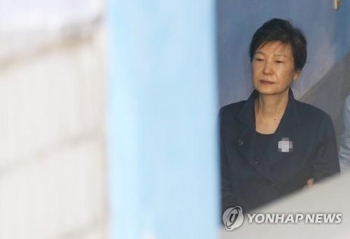 10月13日上午,在首尔中央地方法院,走下囚车的朴槿惠被押往法庭。(韩联社)