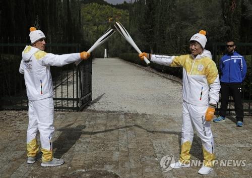 当地时间10月24日,韩国足球运动员朴智星(右)用平昌冬奥火炬接力第一棒火炬手、希腊越野滑雪运动员阿波斯托洛斯・阿格利斯手中的火炬引燃自己手中的火炬。(韩联社)